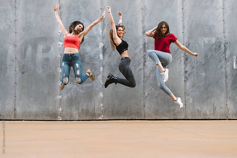 Three women jumping against a wall by Simone Becchetti for Stocksy United