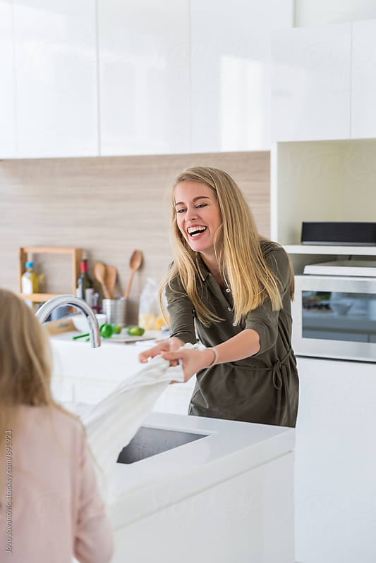 Beautiful mother and her daughter playing in kitchen  by Jovo Jovanovic for Stocksy United