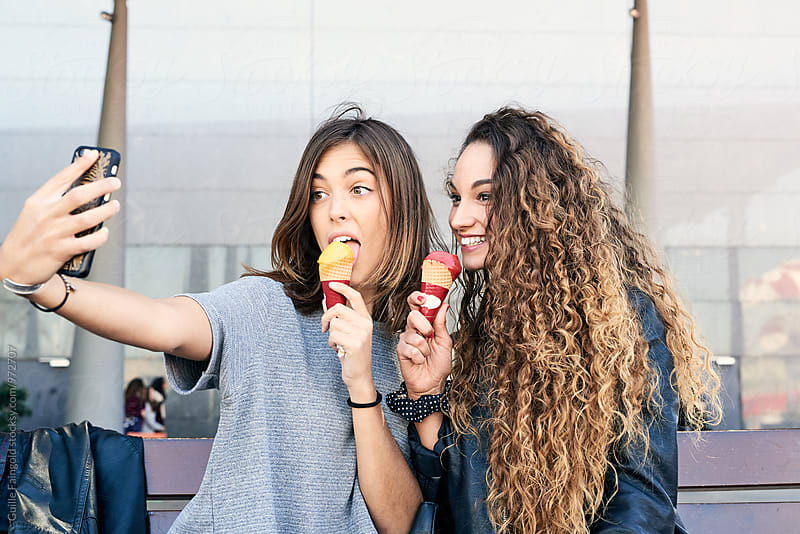 Two girlfriends taking selfie while eating ice cream by Guille Faingold for Stocksy United