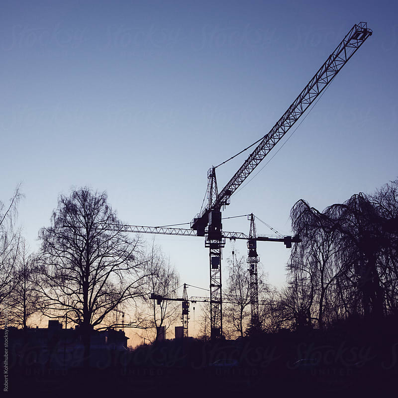 Construction cranes at sunset by Robert Kohlhuber for Stocksy United