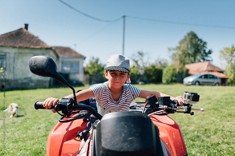 Boy having fun on the quad bike by Boris Jovanovic for Stocksy United