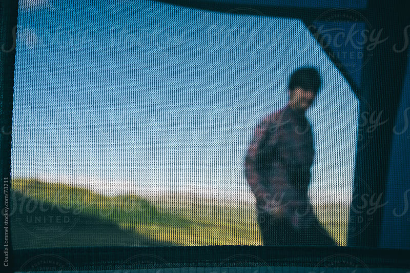 Man (blurred) standing in front of a Tent. View through the Mosquito Net of a Tent (focus) by Claudia Lommel for Stocksy United
