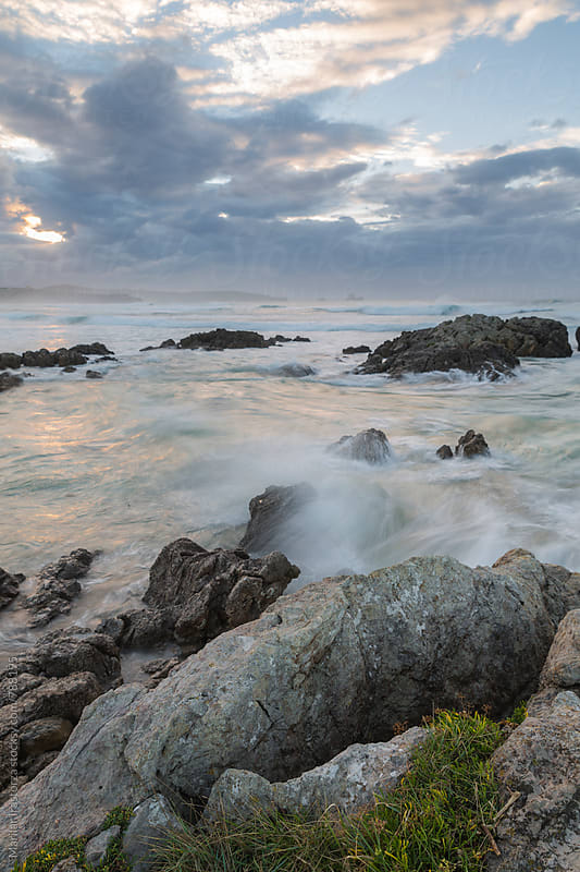 Waves crashing against a rocky shore at sunset by Marilar Irastorza for Stocksy United