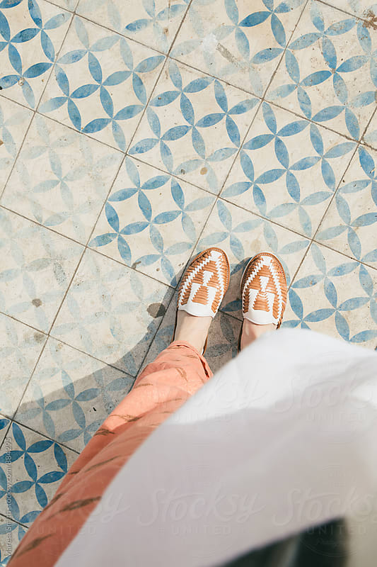 'From where I stand' style photo of woven plimsoles standing on blue patterned tiles by Maresa Smith for Stocksy United