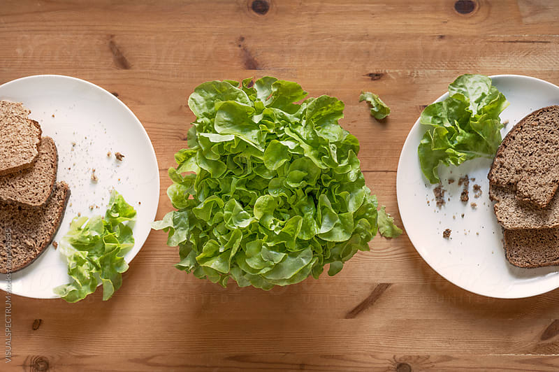 Bread And Lettuce On Wooden Table by VISUALSPECTRUM for Stocksy United