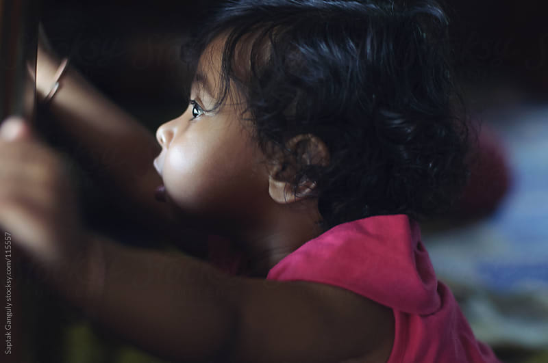 Baby girl looking through a small gap in window,side view by Saptak Ganguly for Stocksy United