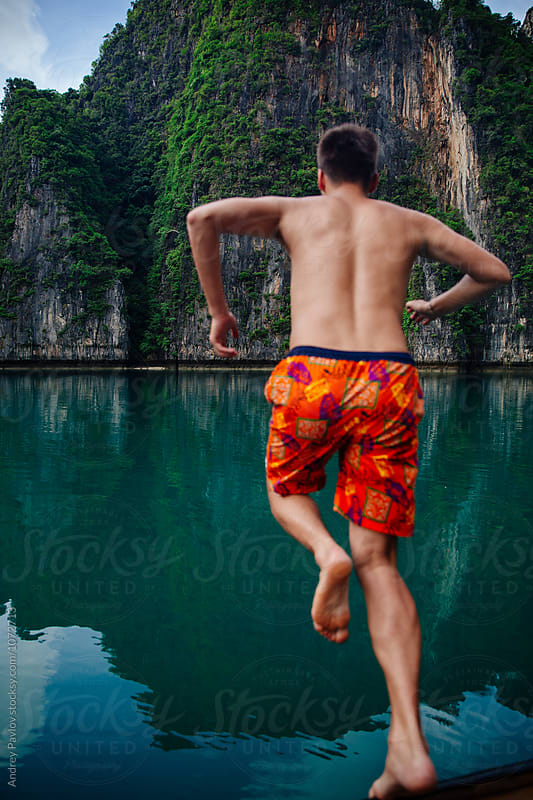 back view of man jumping from boat by Andrey Pavlov for Stocksy United