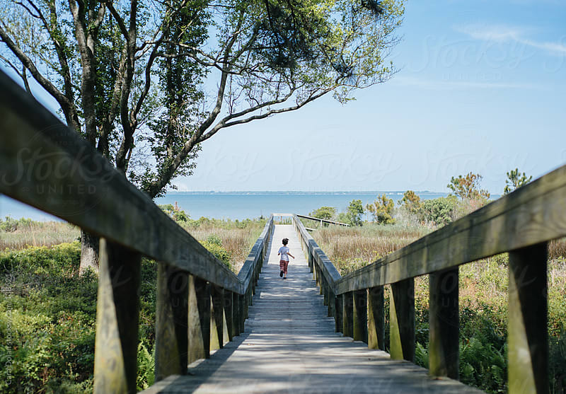 Boy runs down a boardwalk across a marsh to a beach by Cara Dolan for Stocksy United