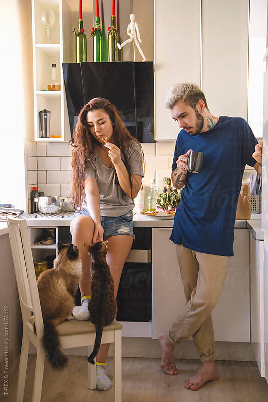 Couple standing in the kitchen, woman feeding cats by Danil Nevsky for Stocksy United