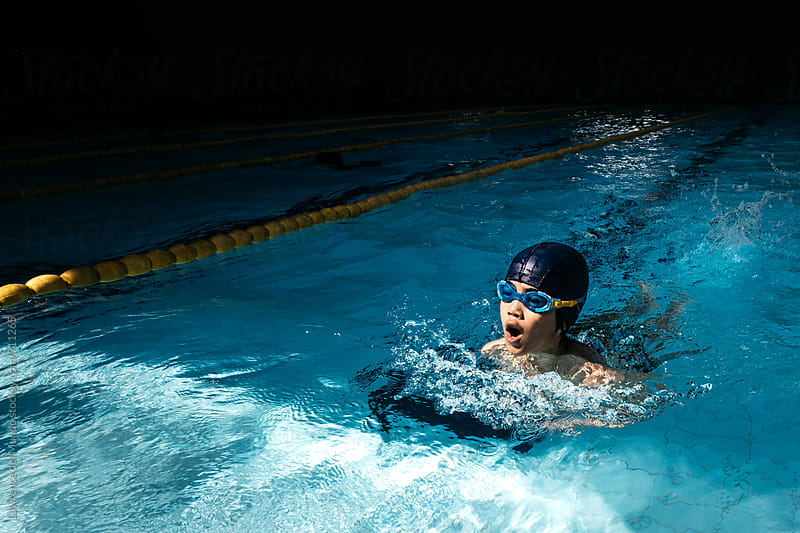 A young swimmer nearing the finish in a breast stroke event for a swimming competition. by Lawrence del Mundo for Stocksy United