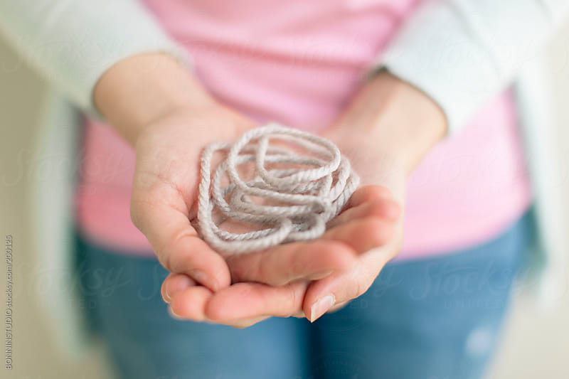 Close-up of woman with pink shirt playing holding wool rope. by BONNINSTUDIO for Stocksy United