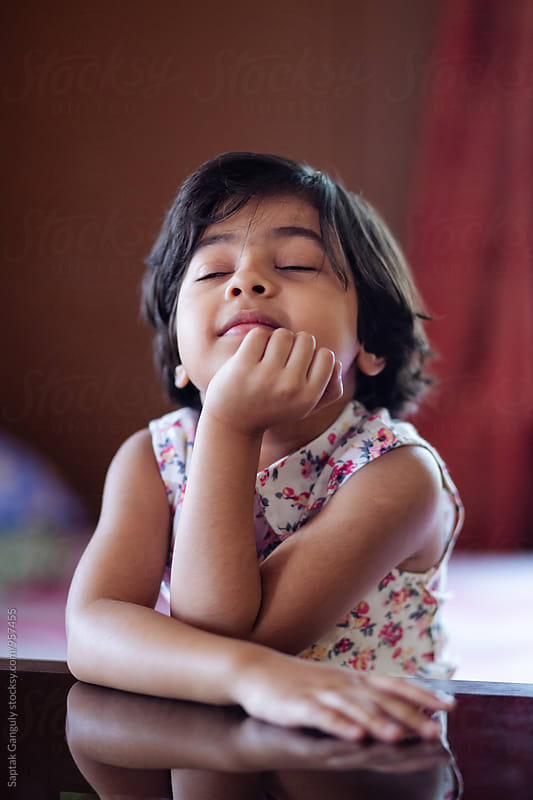 Little girl thinking deeply with closed eyes by Saptak Ganguly for Stocksy United