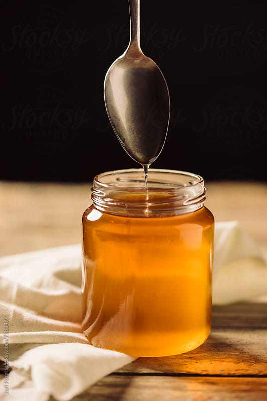 a spoon dropping honey by Juri Pozzi for Stocksy United
