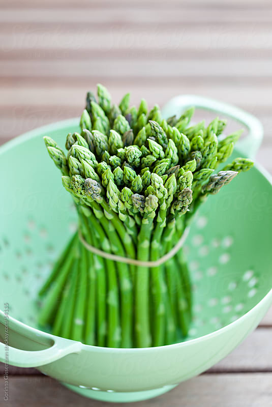 a group of fresh green thai asparagus in a colander on wooden table by Corinna Gissemann for Stocksy United