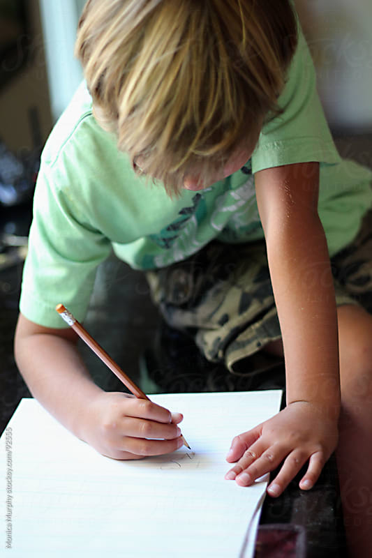 Young boy doing his homework, writing with pencil by Monica Murphy for Stocksy United