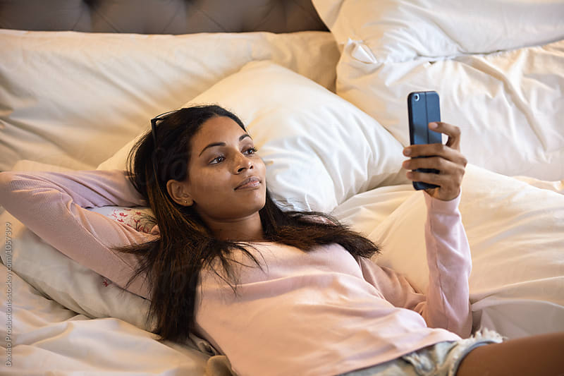 Young woman lying in bed using her mobile cell phone by Daxiao Productions for Stocksy United