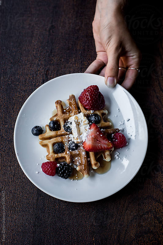 A Waffle Dish With Berries And Syrup by Evan Dalen for Stocksy United
