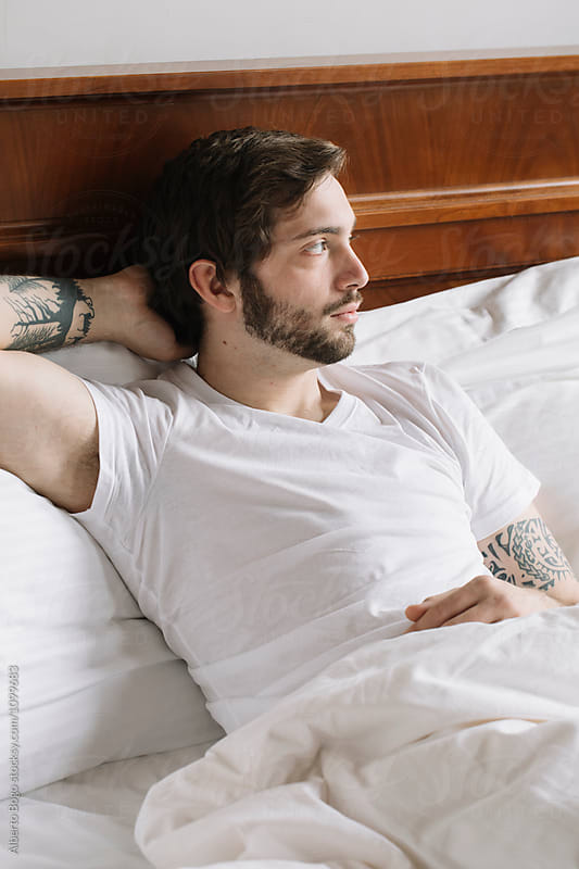 Young man with tattooes on bed in morning by Alberto Bogo for Stocksy United
