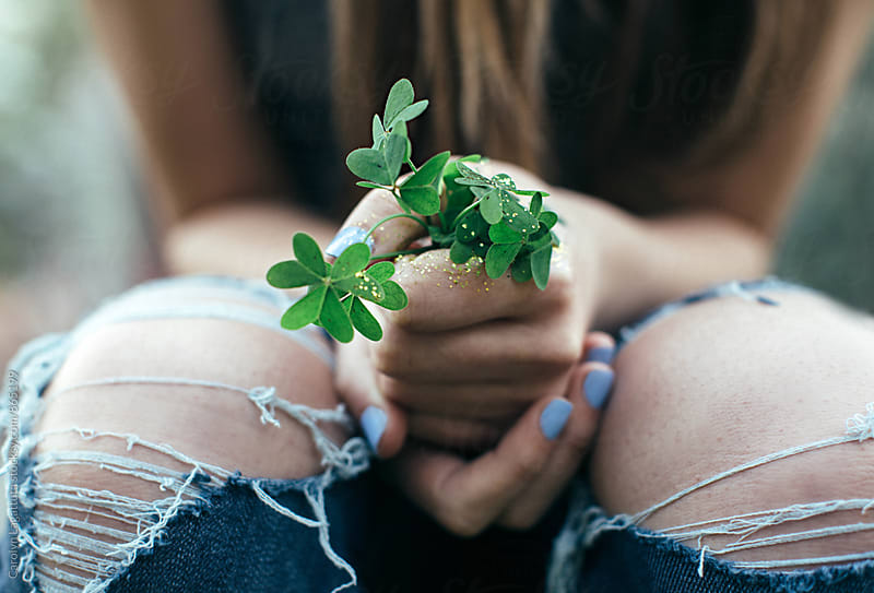 Teenage girl in ripped pants holding a bunch of clover with some glitter by Carolyn Lagattuta for Stocksy United