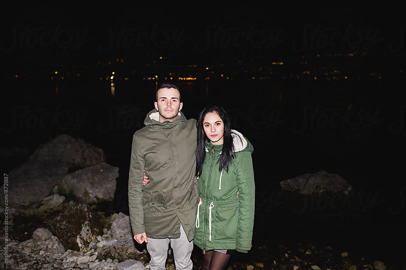 Portrait of couple standing by the lake at night by michela ravasio for Stocksy United
