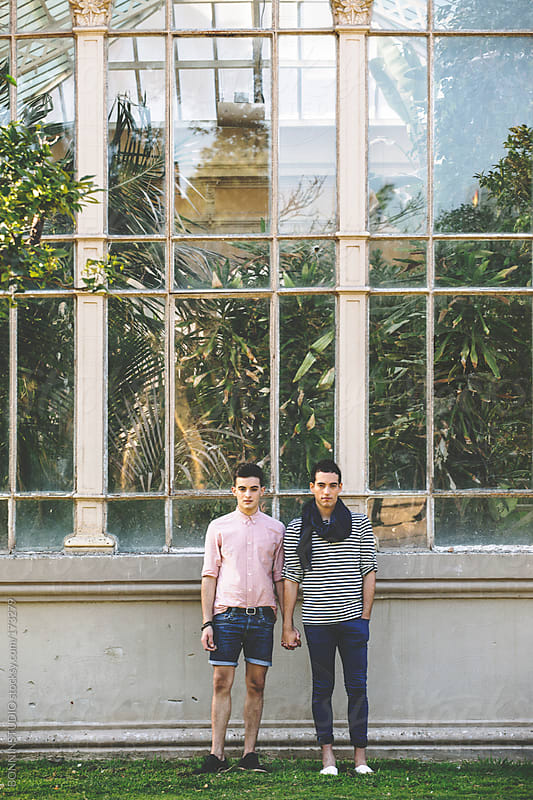 Young gay couple holding hands in front a greenhouse.  by BONNINSTUDIO for Stocksy United