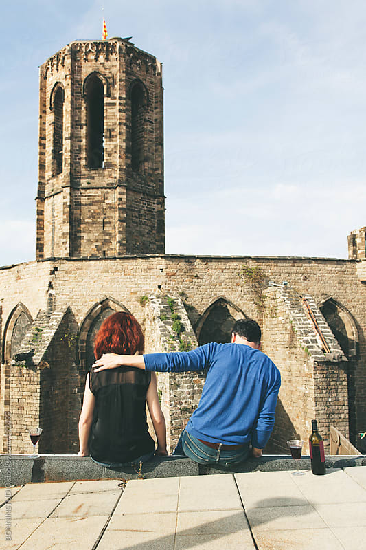 Beautiful couple drinking wine on the rooftop in front a romanic church. by BONNINSTUDIO for Stocksy United