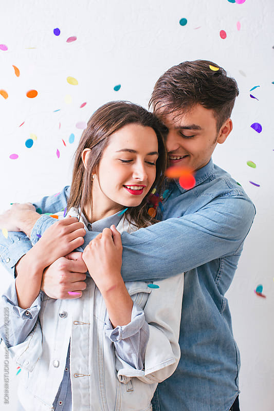 Portrait of young couple embracing as confetti falls from above. by BONNINSTUDIO for Stocksy United