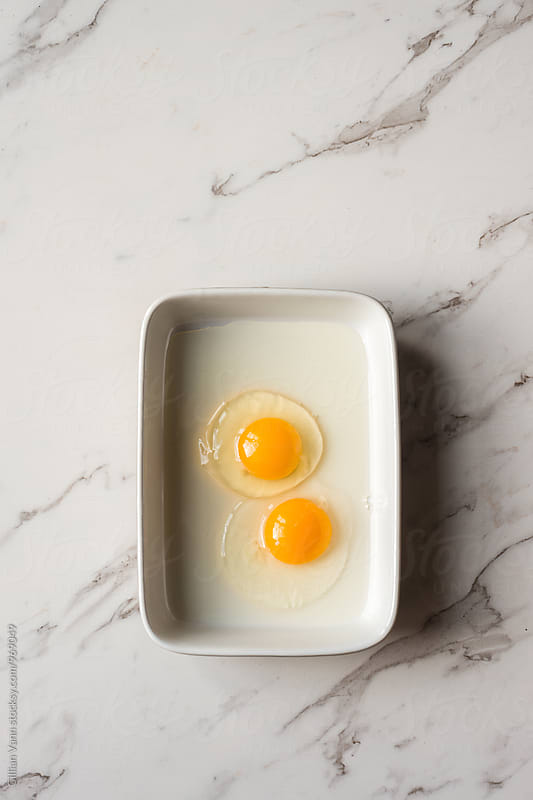 two raw eggs in a rectangle dish by Gillian Vann for Stocksy United