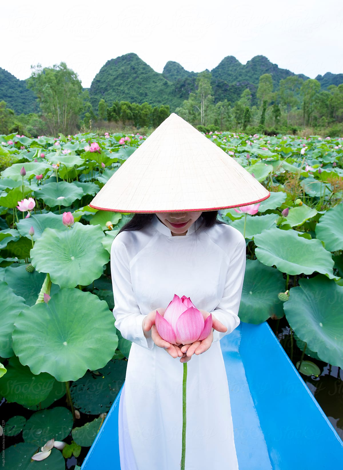 Vietnamese woman in traditional dress with lotus flowers vietnam vietnamese woman in traditional dress with lotus flowers vietnam by hugh sitton for stocksy mightylinksfo