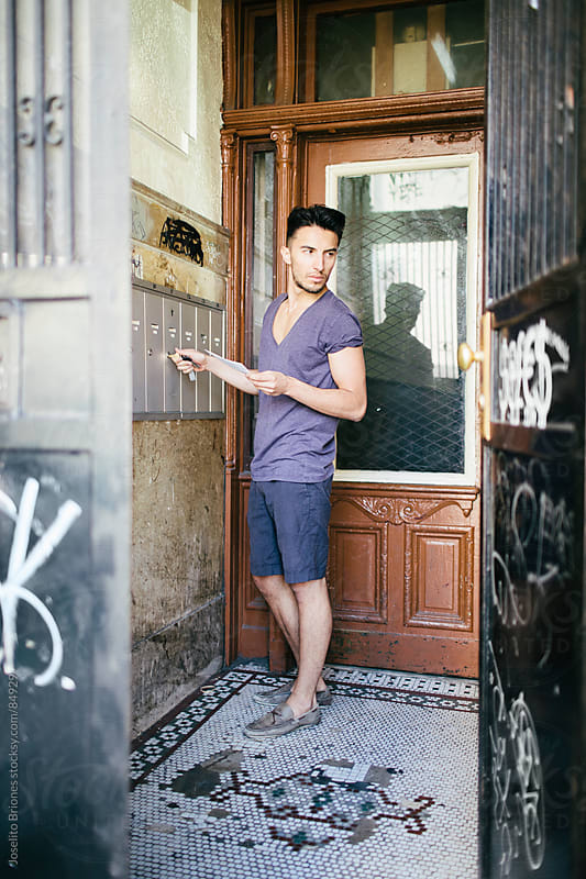 Young Man Collecting Mail in Old Apartment Building in New York by Joselito Briones for Stocksy United