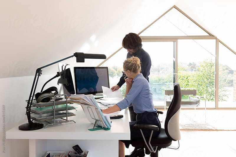 Couple working from home in their modern home office. by Paul Phillips for Stocksy United
