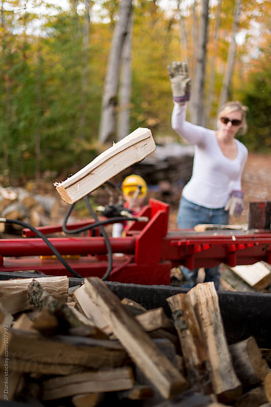 Woman Stacking Firewood for Winter Fireplace in Autumn at Cottage by JP Danko for Stocksy United
