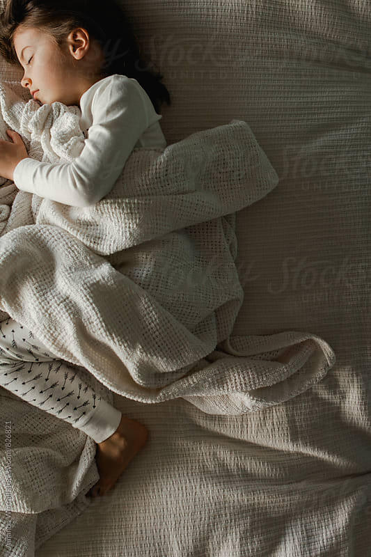 Dimly lit sleeping girl in cozy bedding by Amanda Worrall for Stocksy United