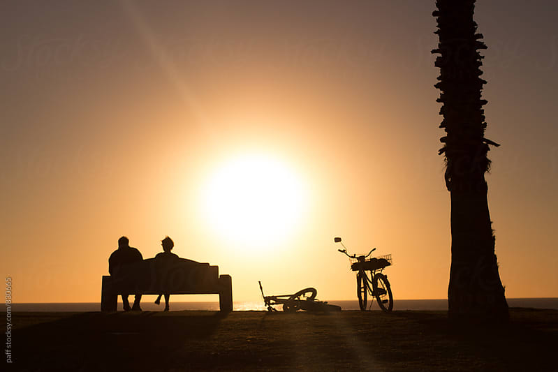 Young couple relaxing on a bench next to the beach at sunset by paff for Stocksy United