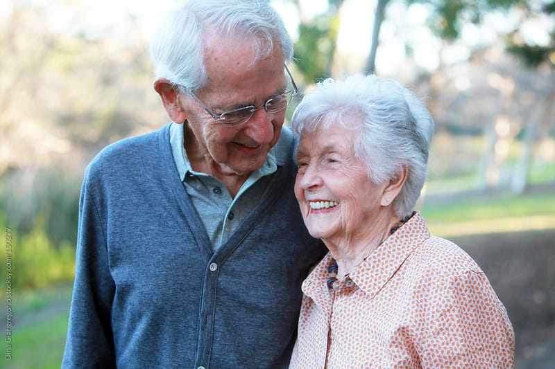Senior couple in park smiling by Dina Giangregorio for Stocksy United