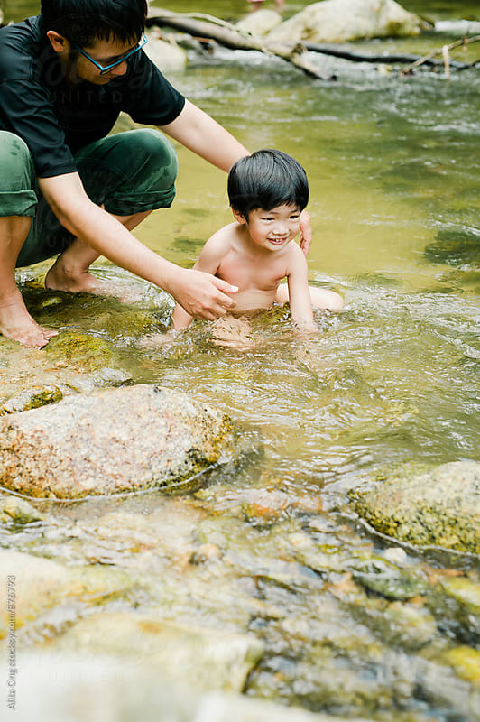 Father and child having fun outdoor in nature by Alita Ong for Stocksy United