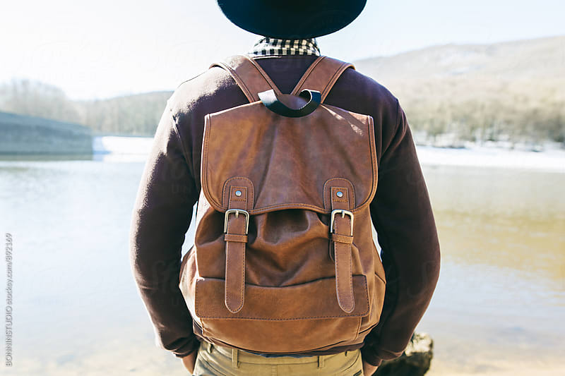 Back view of a mountaineer wearing a leather backpack in front of a lake. by BONNINSTUDIO for Stocksy United