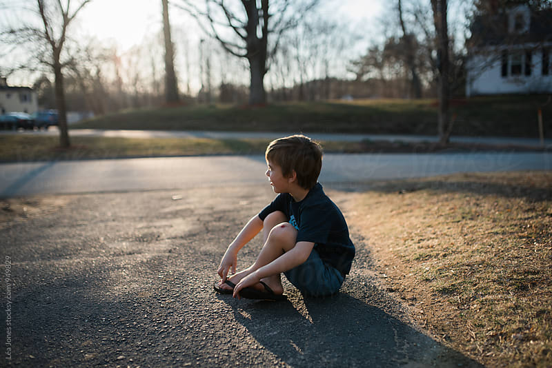 boy siting on driveway by Léa Jones for Stocksy United
