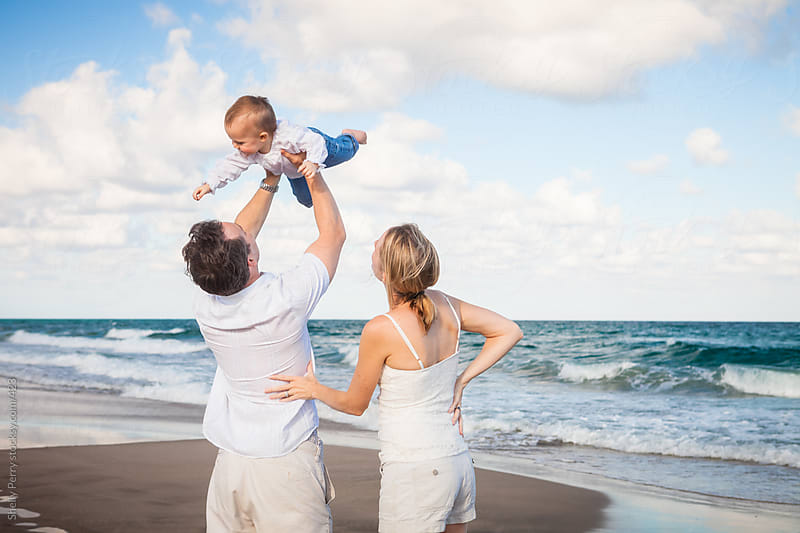 Family of Three; Dad Holding Smiling Toddler Aloft Up to the Sky at the Beach by Shelly Perry for Stocksy United