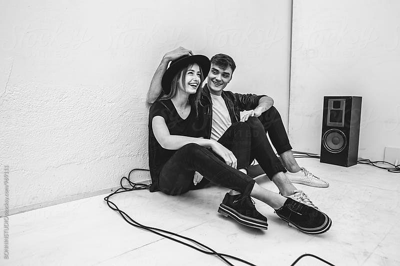 Rocker couple smiling sitting at their recording studio. by BONNINSTUDIO for Stocksy United