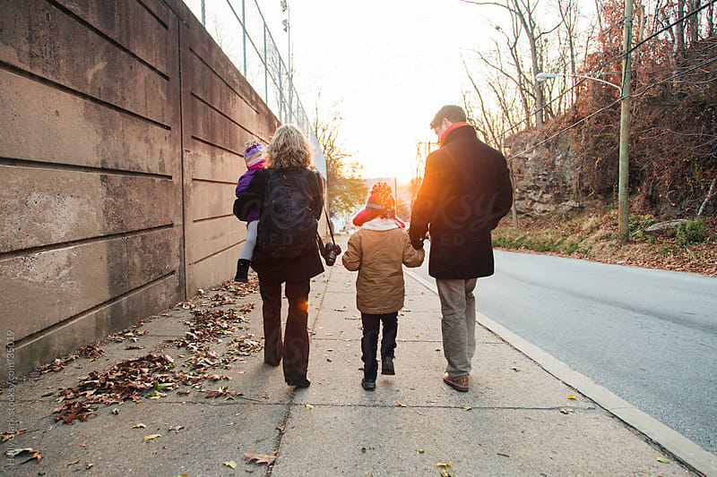 Family Walks Down City Street at Sunset by Holly Clark for Stocksy United