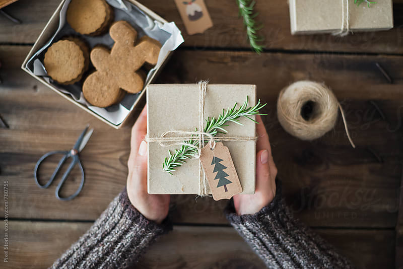 Woman holding gift-wrapped Gingerbread men cookies by Pixel Stories for Stocksy United