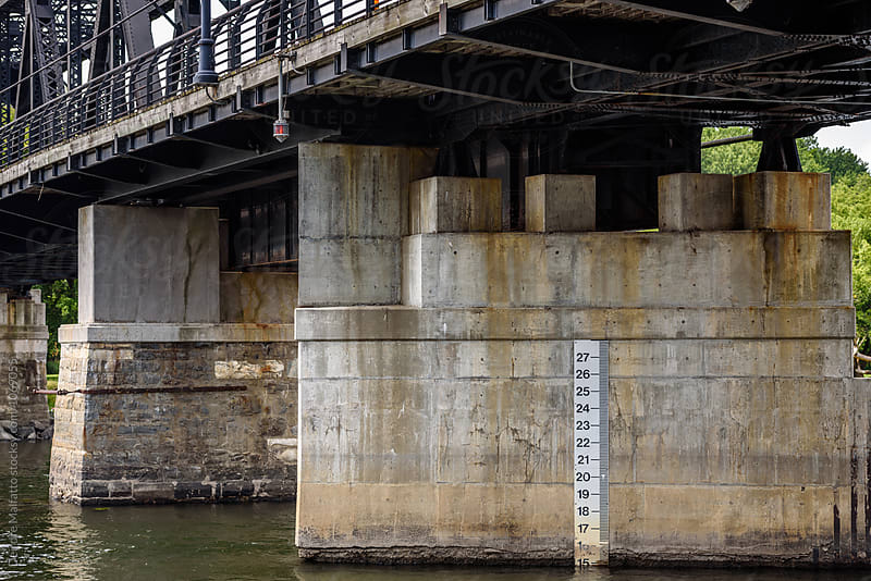 water level indicator under truss bridge by Deirdre Malfatto for Stocksy United