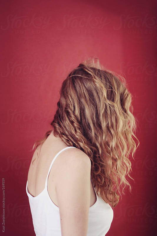 Redheaded young woman in front of a red wall, turned away from the camera by Kaat Zoetekouw for Stocksy United