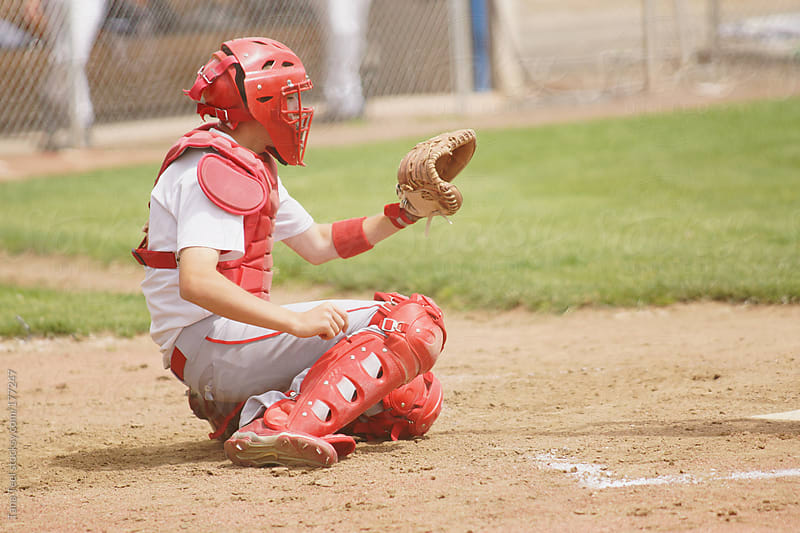 A catcher in a low stance behind the home plate by Tana Teel for Stocksy United
