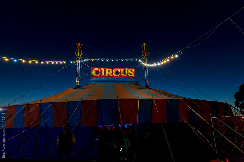 Exterior view of circus tent with lights at dusk by Ben Ryan for Stocksy United