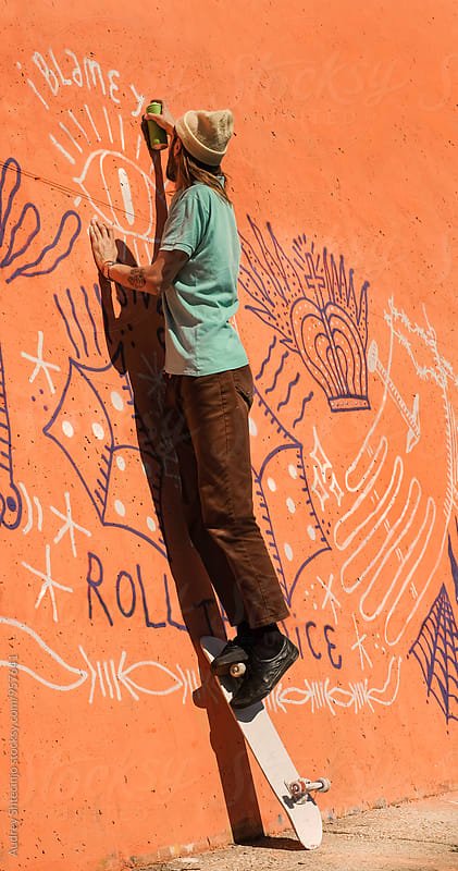 Young hip male spraying graffiti on wall during sunny day by Audrey Shtecinjo for Stocksy United