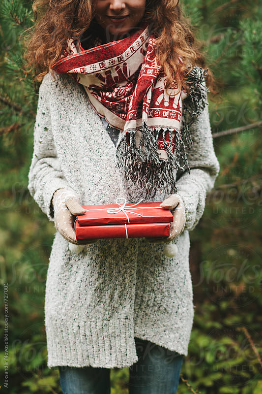 Young woman holding christmas presents wrapped in red paper by Aleksandar Novoselski for Stocksy United