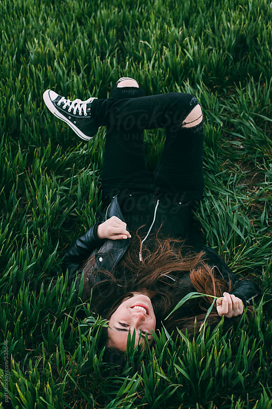 Girl lying on green grass by paff for Stocksy United