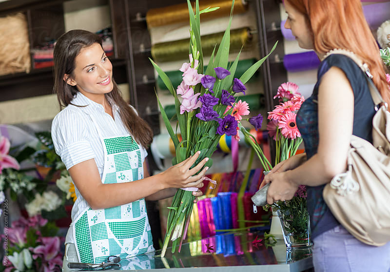 Florist selling flowers to the customer. by Mosuno for Stocksy United